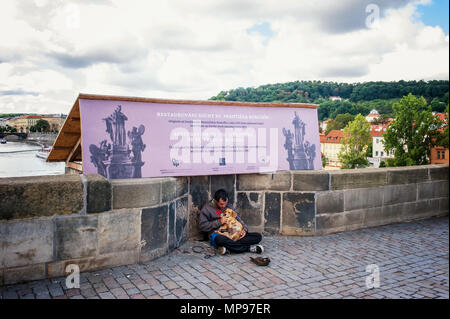 Prague 13.08.2013. A homeless young man with a big black dog on the street asking passersby for money. The horizontal frame. - Stock Photo