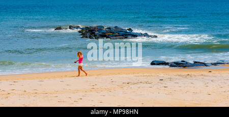 Spring Lake, NJ USA -- May 20, 2018. A young woman walks on the beach in Spring Lake. - Stock Photo
