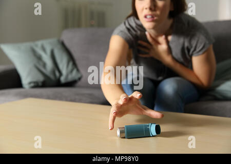 Asmathic girl catching inhaler having an asthma attack sitting on a couch in the living room at home - Stock Photo