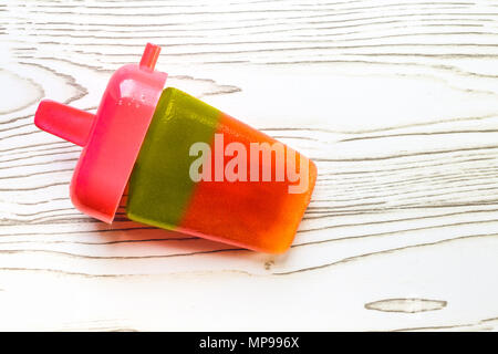 Homemade red and green watermelon popsicle on wooden backdrop - Stock Photo