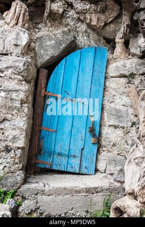 Old crooked blue wooden door in Crete, Greece - Stock Photo