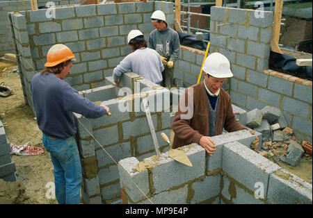 Architecture, Construction, Men working on building site wearing hard hats laying courses of concrete blocks. - Stock Photo