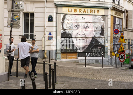 Three men chatting on the street of Belleville neighbourhood in Paris, France, next to a wall with graffiti. - Stock Photo