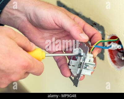 Closeup of electrician's hands installing wall socket - Stock Photo
