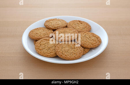 Apple pie crust cookies on a white plate atop a wood table. - Stock Photo