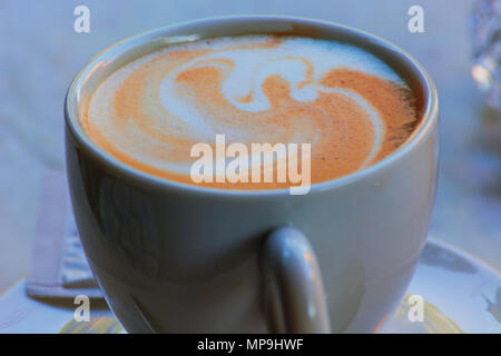A white cup of coffee latte art before bokeh background - Stock Photo