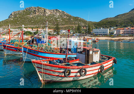 Fishing boats in the harbor of Kalk Bay with the Table Mountain range in the background near Cape Town, Western Cape Province, South Africa. - Stock Photo