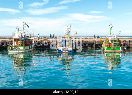 Fishing boats in the harbor of Kalk Bay in the early morning with fishermen in the background, Cape Town, Western Cape Province, South Africa. - Stock Photo