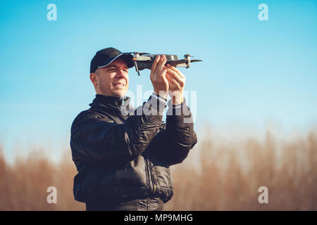 Handsome young man holding the drone, calibrating and preparing for take off. - Stock Photo