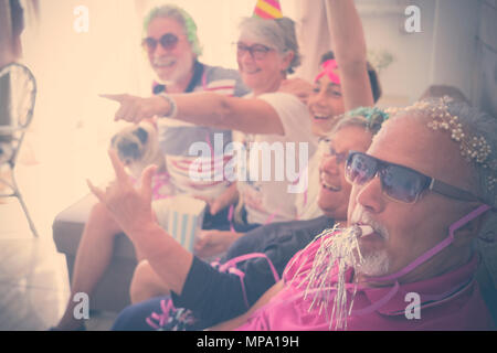 grandfathers group of people celebrating at home with hats and more. smiles and fun from senior to young boy. pug with them. seniors and teenager indo - Stock Photo