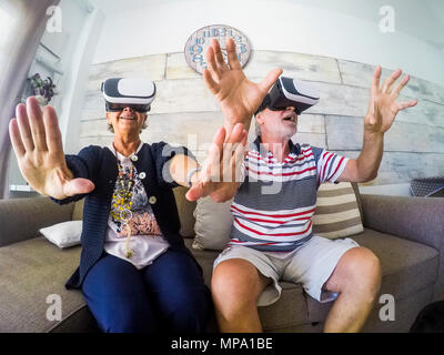 Couple of aged man and woman senior elderly play at home on the sofa with goggles headset trying virtual reality video games and vides. Activityies at - Stock Photo