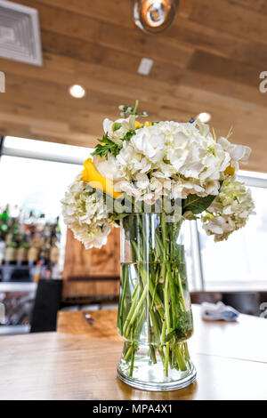 Closeup of one wedding flower bouquet arrangement on wooden table of reception dinner in restaurant venue, alcohol bar background - Stock Photo