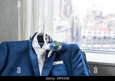 Men's suit and tie groom closeup with flower boutonniere, pin wedding preparation, pocket handkerchief, window with view of urban New York City NYC Ma - Stock Photo