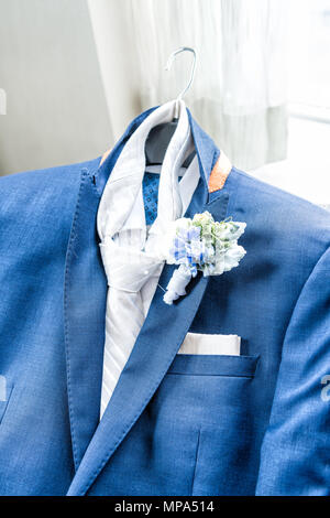 Men's new marine navy blue suit and tie groom closeup with flower boutonniere, pin getting ready wedding preparation isolated, pocket handkerchief - Stock Photo
