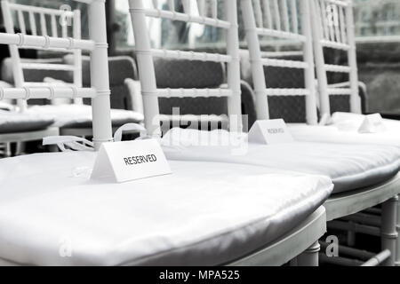 Closeup of white wedding chairs with reserved signs for ceremony with background of rows of many seats pattern, nobody - Stock Photo