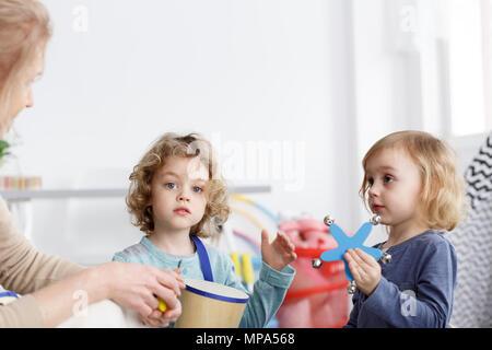 Preschool boy and girl playing the instruments in kindergarten - Stock Photo