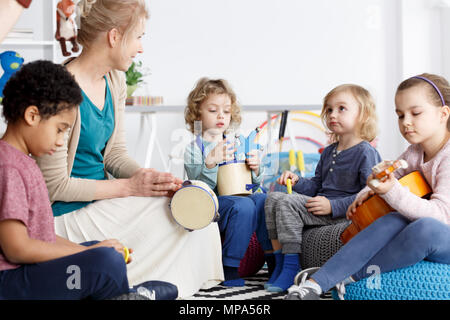 Four preschoolers having fun in kindergarten playing the instruments - Stock Photo