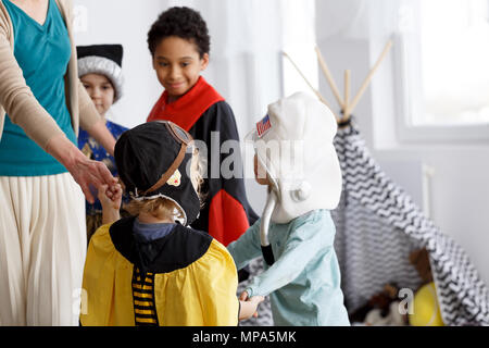 Group of children in costumes dancing in a circle - Stock Photo
