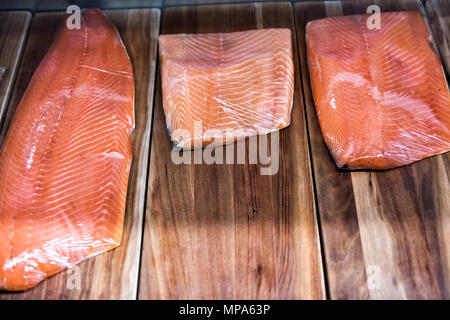 Large smoked raw salmon fillet cut on stand in seafood market shop store on display wrapped in plastic - Stock Photo