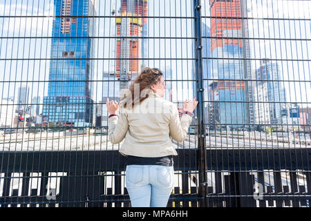 Back of young hipster millennial woman looking at Hudson Yards in NYC New York City Manhattan downtown on high line park and trains behind fence, tour - Stock Photo