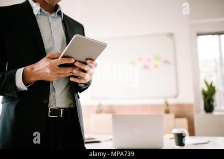 Man operating digital tablet standing in his office room with computer and coffee glass on the table. Close up of man dressed in formals standing in h - Stock Photo