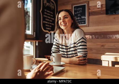 Smiling woman sitting in a restaurant talking to her friend. Friends sitting at a cafe with coffee and snacks on the table. - Stock Photo