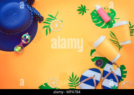 Summer vacation flat lay with tropical leaves, a refreshing drink, sunglasses, sunscreen, flip-flops, hat on a sunny yellow background with copy space - Stock Photo