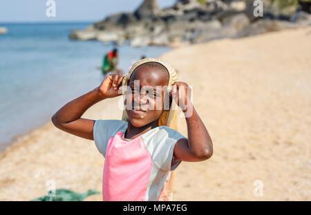 Local young African girl posing while washing clothes on the lakeside beach at Kaya Mawa, Likoma Island, Lake Malawi, Malawi, south-east Africa - Stock Photo