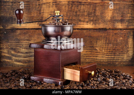 Traditional wooden coffee mill grinder with roasted coffee beans and wooden background. Retro and Vintage Food and drink concept - Stock Photo