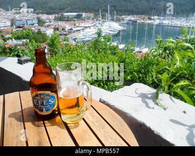 A glass of Efes Pilsen beer with Marmaris marina in the background - Stock Photo