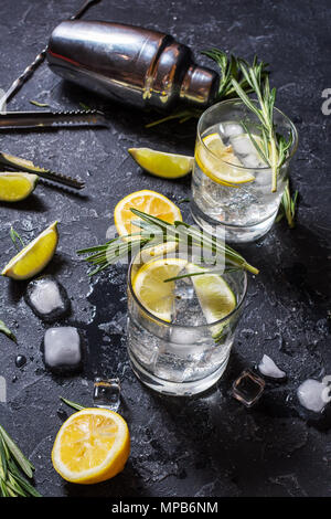 Alcoholic drink gin tonic cocktail with lemon, rosemary and ice on stone table. - Stock Photo