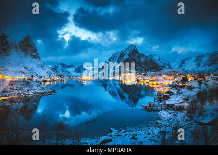 Classic view of the famous fishing village of Reine with Olstinden peak in the background in magical winter evening twilight, Lofoten Islands, Norway - Stock Photo