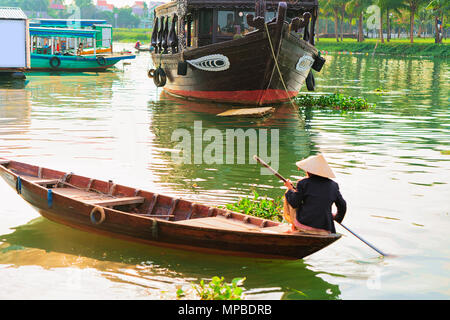 Senior woman in traditional vietnamese hat in a boat on Thu Bon River in Hoi An, Vietnam - Stock Photo