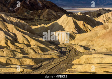 Sunrise Golden Valley - Golden morning sunlight shining on a colorful valley at the Badlands of Death Valley National Park, California, USA. - Stock Photo