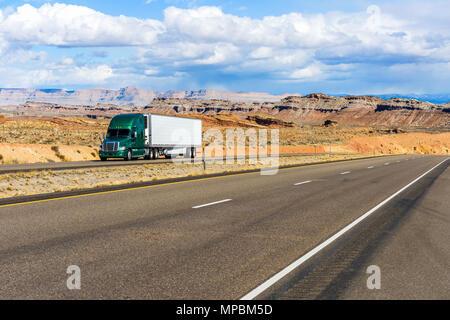 Desert Highway - A semi-trailer truck driving on Interstate Highway I-70 in colorful desert land, Utah, USA. - Stock Photo