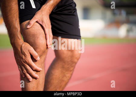 knee Injuries. young sport man with strong athletic legs holding knee with his hands in pain after suffering muscle injury during a running workout tr - Stock Photo