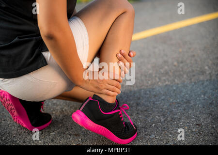 Ankle sprained. Young woman suffering from an ankle injury while exercising and running. Healthcare and sport concept. - Stock Photo