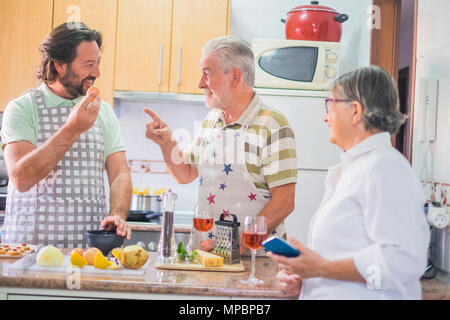 Indoor kitchen scene tiwh a family cooking. Father, mother and son. Senior couple and middle aged male. Joking and telling daily concept. - Stock Photo