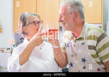 senior man and senior woman with white hair adults having somne fun smiling in the kitchen at home drinking red wine. - Stock Photo