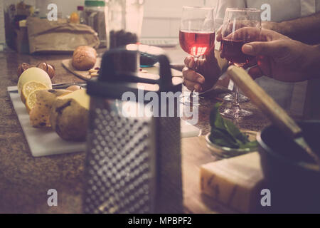 vintage filter for a cocktail home scene with three hands from two men and a woman at home. Domestic scene of usual life for a nice time together. - Stock Photo