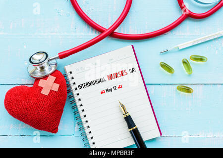 International Nurses Day, May 12. Healthcare and medical concept. Stethoscope, red heart, notepad or notebook, thermometer and yellow Pill on Pastel w - Stock Photo