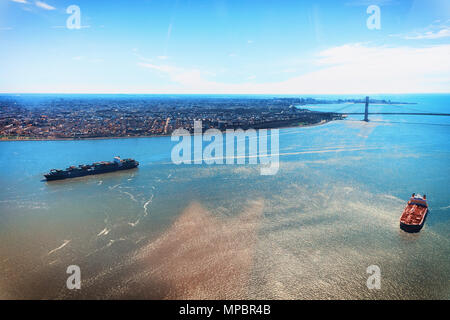 Aerial view on Containers Vessel and Manhattan Bridge structure with New York skyline in the morning over east Hudson River, New York City, USA - Stock Photo
