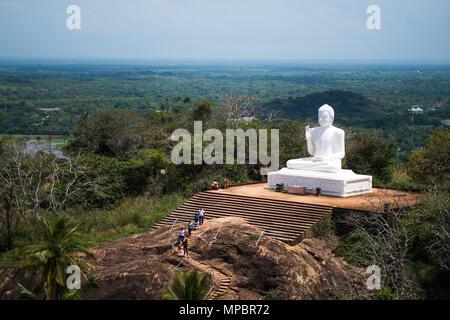 Mihintale, Sri Lanka - 07 May 2018: Big white Buddha statue against blue sky in Mihintale - Stock Photo