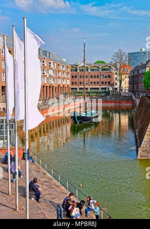 Dusseldorf, Germany - May 3, 2013: Boat at harbor in Dusseldorf in Germany. Tourists nearby. Stock Photo