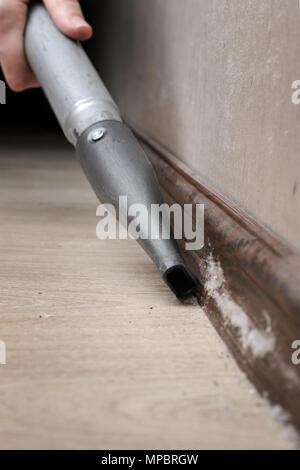 cleaning the accumulated dust with a vacuum cleaner. Woman vacuuming the dirt on the floor of the house - Stock Photo