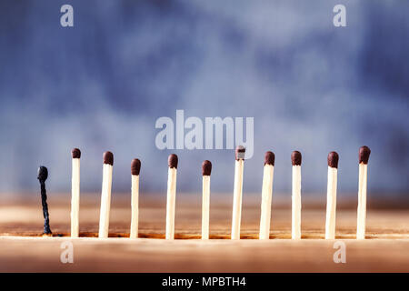 a row of matches on a wooden background, the last match burned down. Extinct match next to unlit - Stock Photo