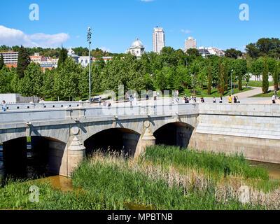 Puente del Rey bridge over the Manzanares river in Madrid Rio at spring day with Principe Pio and Plaza de Espana in background. - Stock Photo