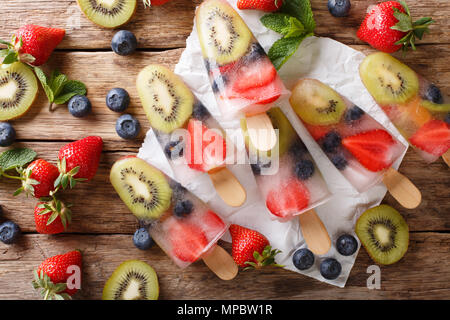 refreshing fruit popsicle lollies with berries, fruits peppermint on wooden background macro. horizontal top view from above - Stock Photo