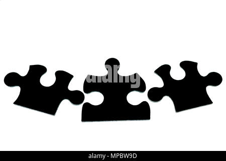 three black pieces of puzzle on a white background isolate. The concept of unity, teamwork - Stock Photo
