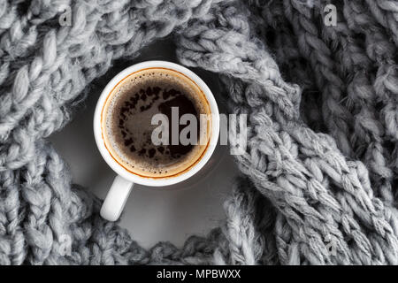 a cup of coffee wrapped in a woolen warm gray scarf. Top view - Stock Photo